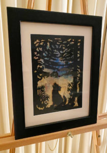 Karen Bell: paper cutting art of a wolf howling in the forest